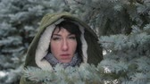 başlık : Sad woman is posing in winter forest and hiding behind fir tree branches