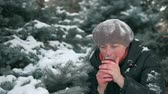 flask : Woman is drinking hot tea in forest, beautiful winter landscape with snowy fir trees.