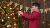 Boy decorating christmas tree, wooden background and lights - Merry Christmas and Happy Holidays! Wideo