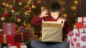 Boy sitting indoor near decorated xmas tree with lights and opening gifts - Merry Christmas and Happy Holidays! Wideo