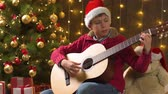 Teen boy playing guitar, sitting indoor near decorated xmas tree with lights, dressed as Santa helper - Merry Christmas and Happy Holidays!