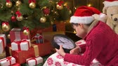Teen boy waiting for Santa and watching the clock, lying indoor near decorated xmas tree with lights, dressed as Santa helper - Merry Christmas and Happy Holidays! Stock mozgókép