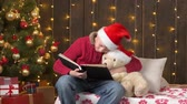 Santa helper boy reading book to bear toy, sitting indoor near decorated xmas tree with lights - Merry Christmas and Happy Holidays! Stock mozgókép