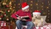 Santa helper boy reading book to bear toy, sitting indoor near decorated xmas tree with lights - Merry Christmas and Happy Holidays! Videos