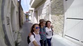 Three young women walking around the old city. Friends, tourists taking a selfie on the background of the city.