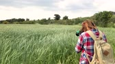 woman s day : Young woman professional photographer taking pictures of the landscape. Field with rye, swaying in the wind.