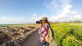 Young woman professional photographer taking pictures of the landscape on the background of ancient ruins in Greece. Wideo
