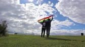 Two young women are kissing on a background of a rainbow flag. The bright sun, LGBT rights, the lesbian family.