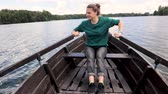 A young beautiful woman is sailing on a boat on the lake. A strong woman paddles with oars. Wideo