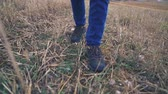 buty : Hiker in close-up slow motion leg shot walks uphill in the field.