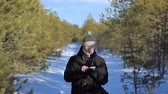 zpráv : The young man walks along the forest path and pokes his finger on the mobile phone. Winter day. The weather is sunny. Dostupné videozáznamy