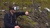 falésias : The artist-tourist in glasses of virtual reality draws a picture. In the background there is a coniferous forest and snowy mountain slopes. Vídeos