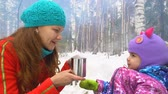 vapor : Mom and her little daughter drink hot tea in the winter forest. In the background smoke from the fire.