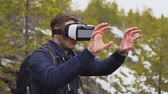 falésias : A tourist with a backpack on his back is standing on the mountainside in virtual reality glasses and waving his arms. In the background there is a coniferous forest and snowy mountain slopes. Vídeos