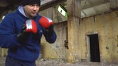 boks : A fight with a shadow. A boxer in a blue sweatshirt trains in an abandoned building.