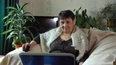 vállkendő : An elderly woman is sitting in a armchair with a laptop on her lap and smiling. Stock mozgókép