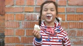 ziegel : Cute little girl is eating ice cream and smiling on a brick wall background. Stock Footage