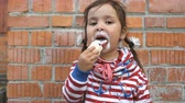 ziegel : Cute little girl is eating ice cream on a brick wall background. Stock Footage