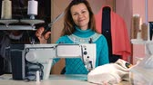 panák : The seamstress sits behind the workplace, smiles and holds scissors in her hands.