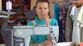 fermuar : A seamstress woman sits at the workplace in sewing studio and thinks. Stok Video