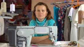 örgütlü : A seamstress woman sits at the workplace in sewing studio and thinks. Stok Video