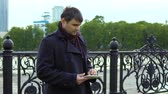 procurar : A man in a black coat is standing next to the city embankment and uses a tablet.