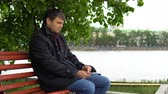 ławka : A man in a black coat sits on a bench in the city park and works with a stylus on the tablet. Wideo