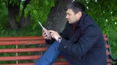 ławka : A man in a black coat sits on a bench in a city park and pokes his fingers on the tablet.