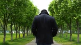 şair : A young man in a black coat walks along the alley of blossoming apple trees in the park. Stok Video