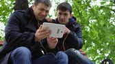 ławka : Two young people sit in a city park on a bench, look at the tablet, smile and talk. Wideo