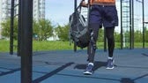 ginásio : The athlete jumps on the bar and jumps back. In the background a street workout park and city landscape. Stock Footage