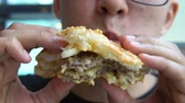 healthy eating : A young man with acne on his face eats hamburger in a fast food restaurant.