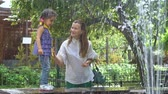 moederdag : Mom with a three-year-old daughter are walking next to a fountain in a public park. Stockvideo