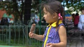 coletas : A little girl eats ice cream in a public park and looks around. Archivo de Video