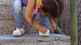 potřísněný : A three-year-old girl wipes her sandals with a wet napkin, standing on the stairs in a public park.