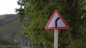 дорожный знак : Road sign. A sharp turn. In the background, trees, mountains and a young man.