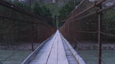 谷 : A fictional character is walking along a swinging suspension bridge that hangs over the river.