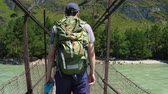 谷 : A tourist with a big green rucksack is walking along a suspension bridge that hangs over the river. Back view. 動画素材