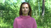 natürliche schönheit : Portrait of a woman in a pink knitted sweater. In the background a blurred forest.