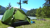 bergwandelen : A green tent of the traveler stands on the bank of a mountain river next to a place for a campfire.