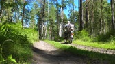 manèges : The fisherman rides a moped along a forest dirt road illuminated by the sun.