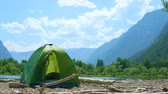 谷 : A tourist tent of green color stands on the sandy shore of a mountain lake, littered with dry logs thrown ashore. Timelapse.