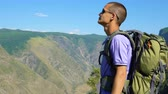 falésias : A young tourist with a backpack and wearing sunglasses stands on the background of a mountain gorge and admires the scenery.