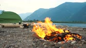 bergwandelen : A fire burns on the shore of a mountain lake in a tourist camp.