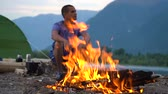 bergwandelen : A tourist sits by the fire on the shore of a mountain lake in a tourist camp. Evening time.