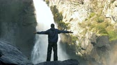 bergwandelen : A traveler is standing in front of a mountain waterfall with arms outstretched.