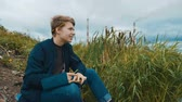 autor : A young writer of attractive appearance sits on the river bank and writes a book. In the background, a cattail, an overcast sky and smoking pipes of a hydroelectric power station. Stock Footage