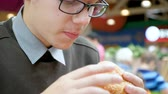 gastritis : A young man in glasses is eating a hamburger in a fast food restaurant in a shopping center. Close up. Stock Footage