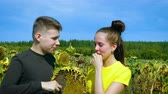 Portrait. A young man and a girl eat sunflower seeds. Vídeos