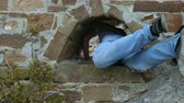 bunda : A young man in a white T-shirt and jeans crawls through a hole in a stone wall.